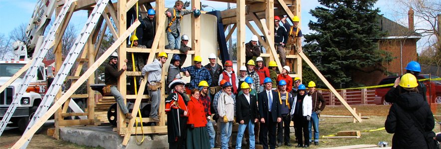 A group of student builders, the town crier, and the mayor standing in front of the framing for the Mammoth Cheese structure