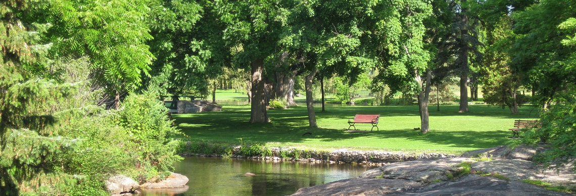 Two park benches overlooking water in park