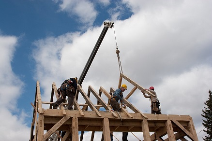 Three construction workers on top of wood structure with crane assembling roof