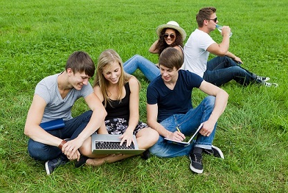 Five teenagers sitting on grass looking at laptop