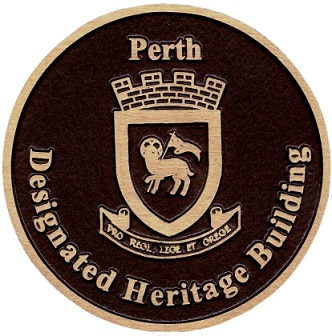 Brown and gold plaque that reads Perth Designated Heritage Building with crest in centre