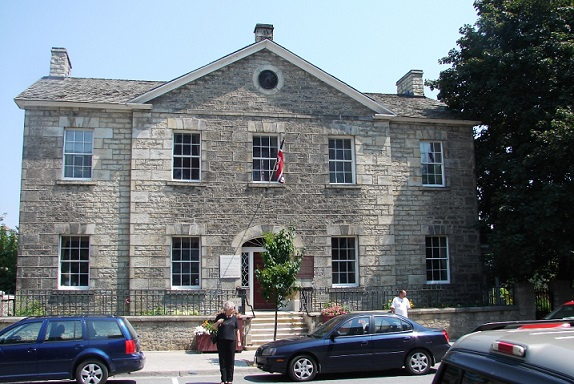 Large grey stone building with maroon door