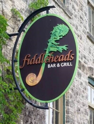 Round sign protruding out of stone building that says Fiddleheads Bar & Grill