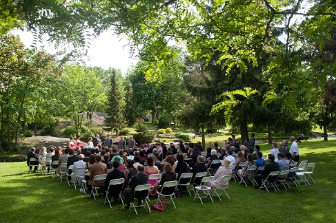 Wedding guests seated at white seats in park surrounded by trees