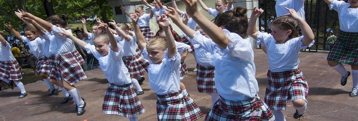 Young girls wearing kilts doing the Highland Fling