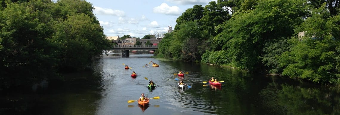 Group of kayakers and canoeists travelling down waterway