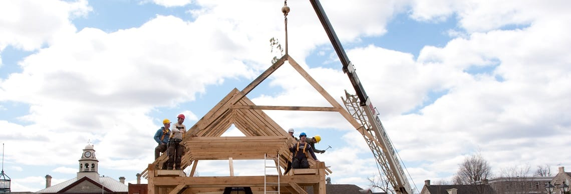 Construction workers on top of wooden structure